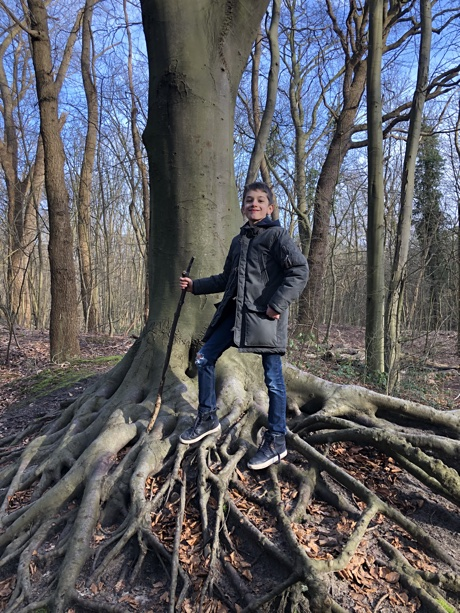 Adam posing in front of a tree with large roots