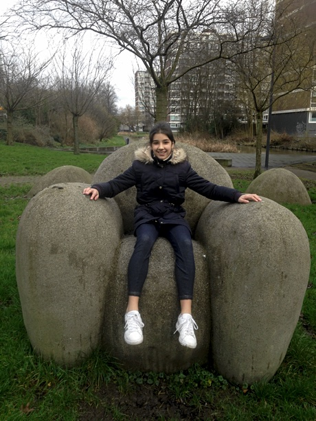 Alice sitting in a stone chair